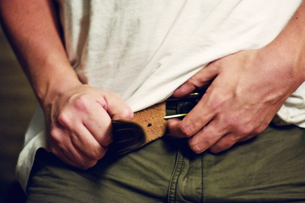photo of hands fastening belt buckle