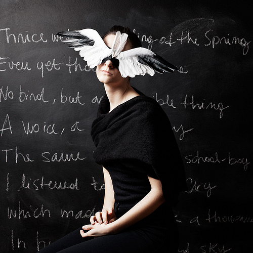 photo of a woman dressed in black sitting in front of a chalkboard