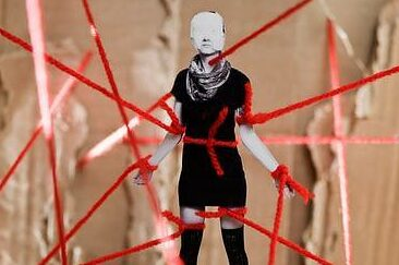 photo of miniature woman tied up with red yarn