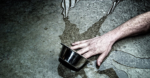 photo of hand tipping over silver bowl containing water