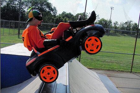 photo of man driving a very small car at a skate park