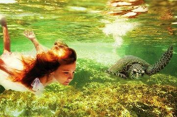 image of girl swimming underwater with a sea turtle