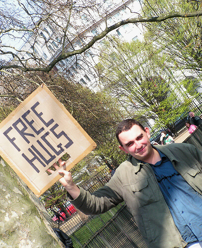 "photo of man holding sign that says ""FREE HUGS"""