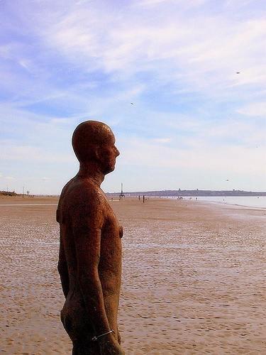 metal man statue on a beach