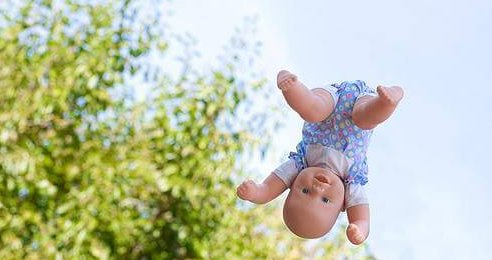 photo of a baby doll in midair