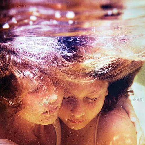 photo of two children hugging underwater