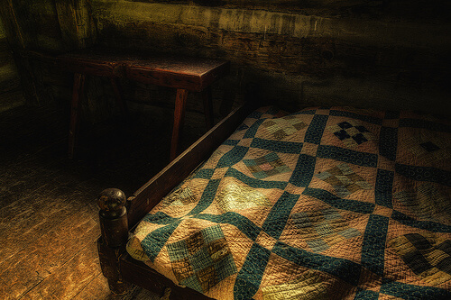 photo of antique bed with quilt on top and bench at foot of bed