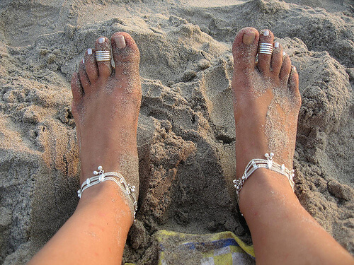 photo of sandy feet with rings on toes