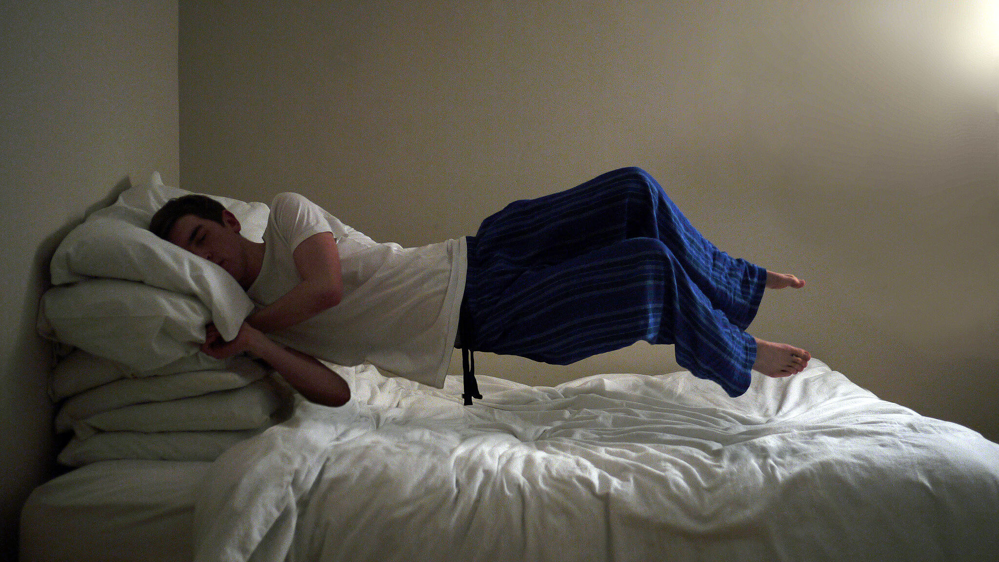 photo of sleeping man floating above bed