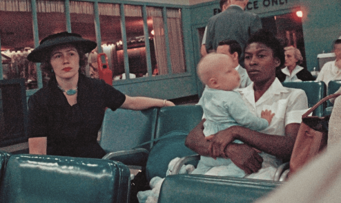 photo of a woman seated next to a nanny holding a baby in an airport