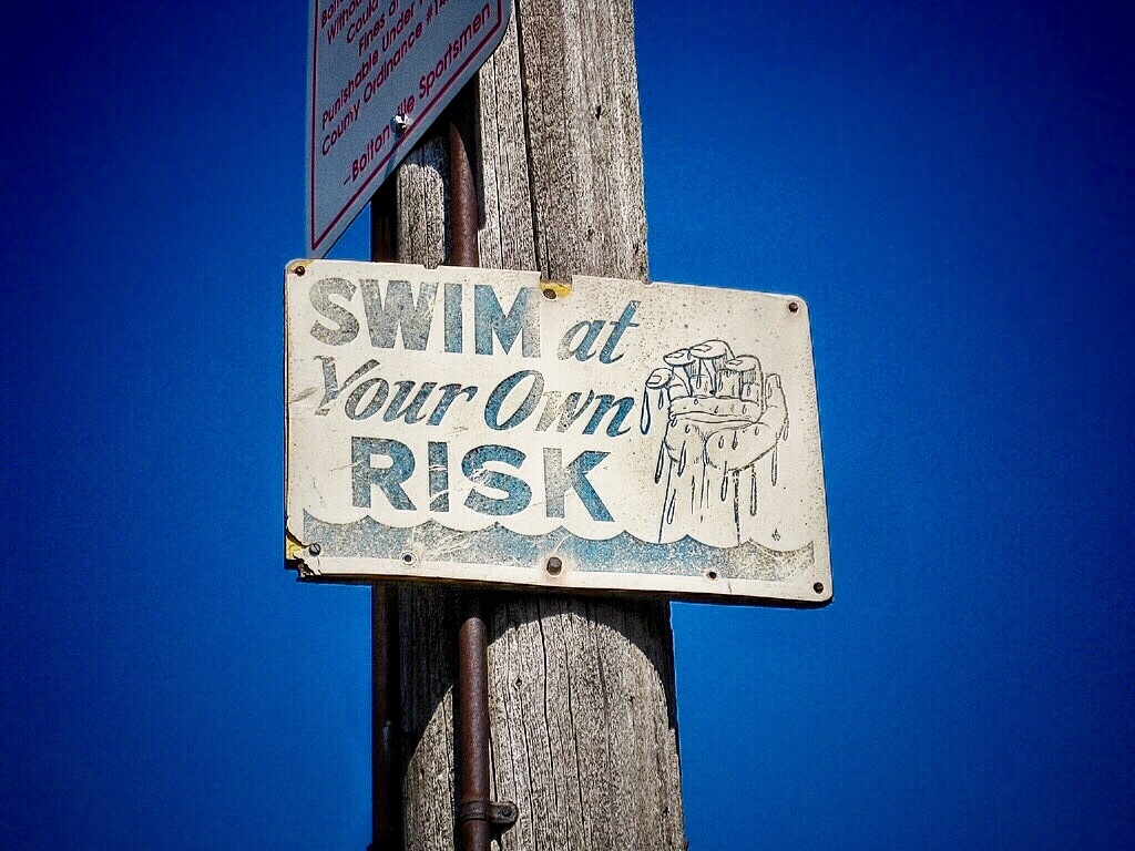 """Swim at your own risk"" sign nailed to post"