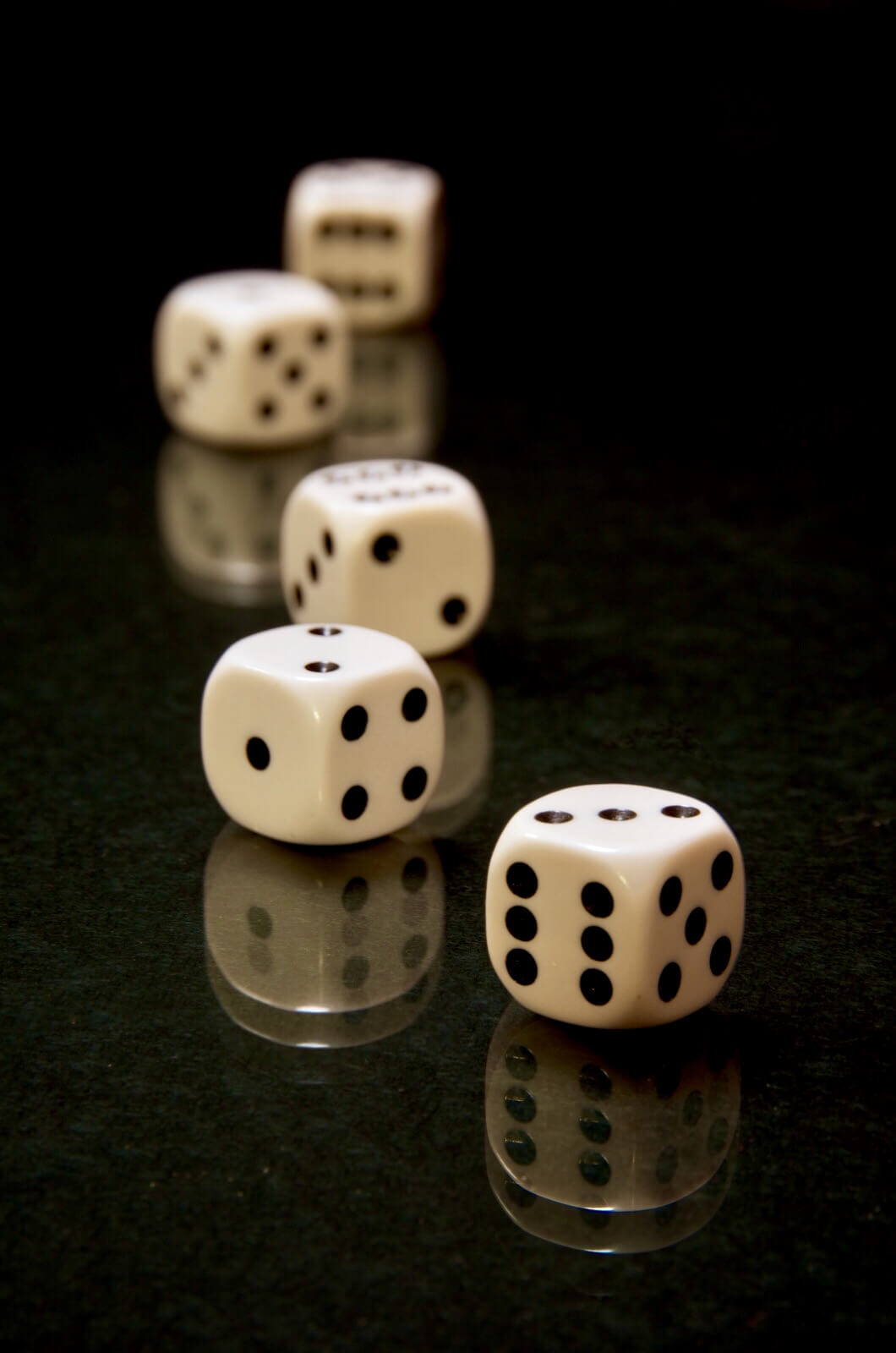 five black & white die on a dark surface