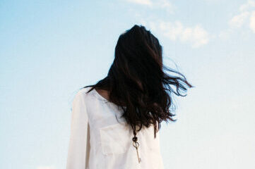 photo of girl with dark hair covering her face