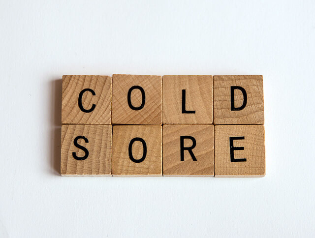 "photo of Scrabble letters that spell out ""cold sore"""