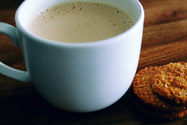 photo of latte on a wooden table next to two cookies