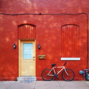 photo of red brick wall with bicycle parked in front