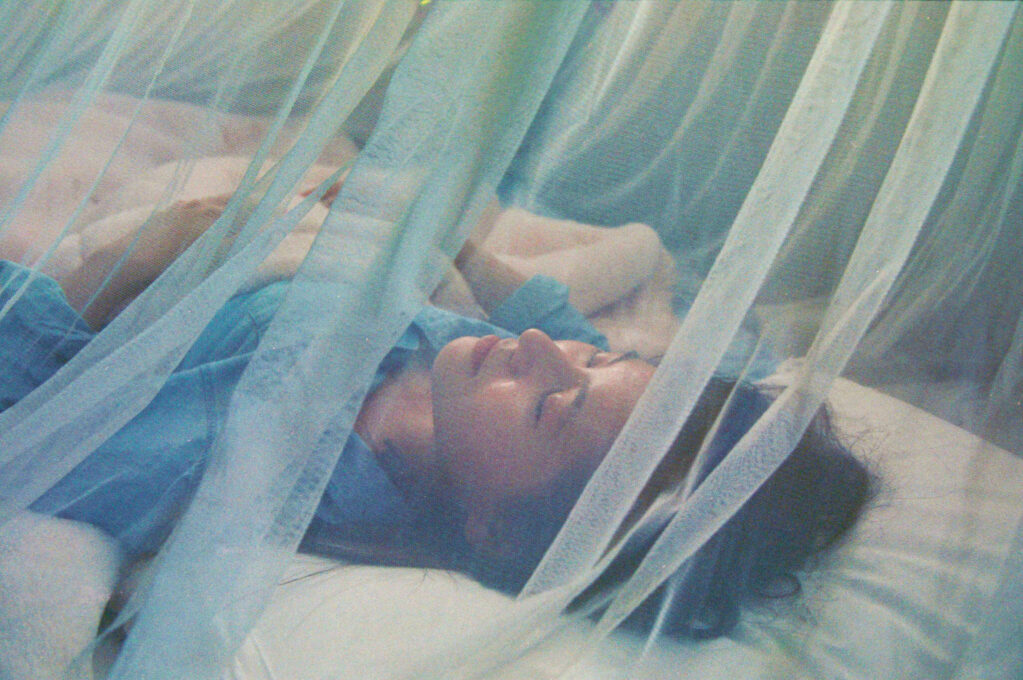 photo of woman sleeping under mosquito net