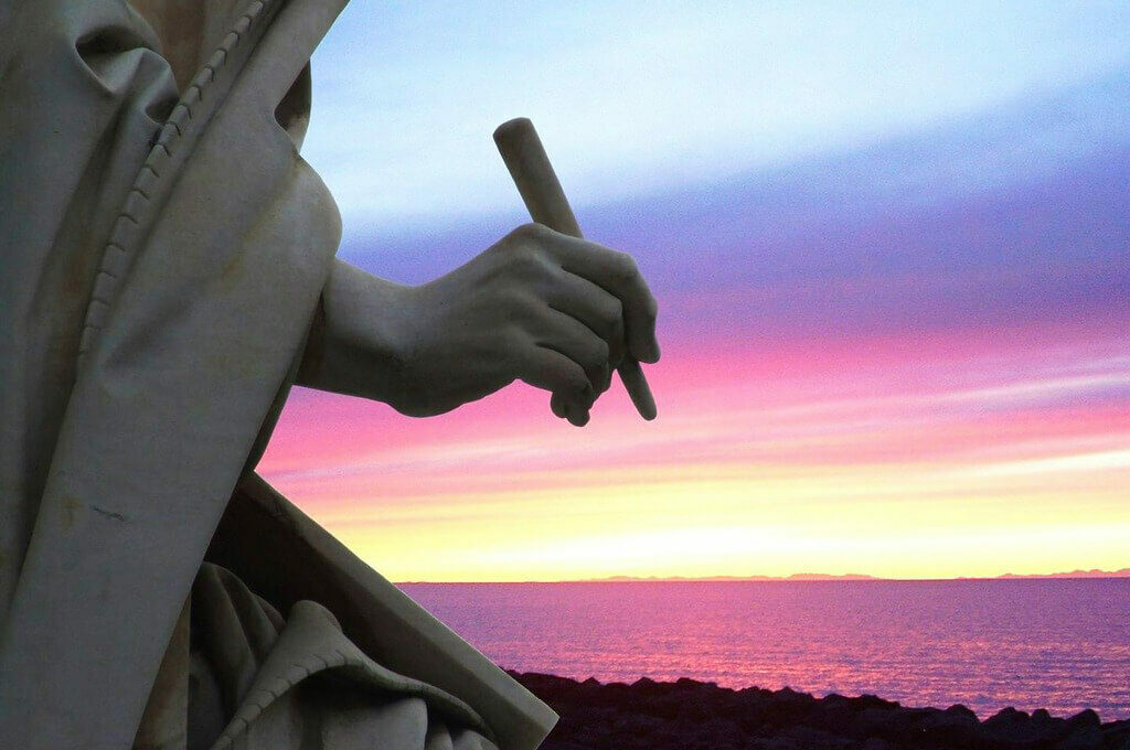 photo of a statue's hand holding a writing implement