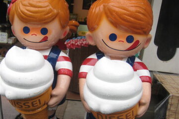 photo of two statues holding ice cream cones