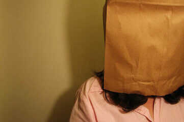 photo of woman with paper bag on her head