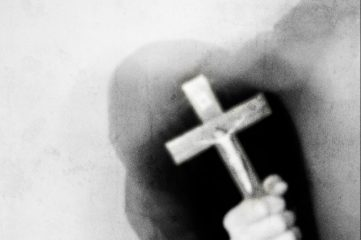 photo of mysterious figure holding up a cross