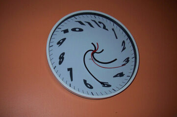 photo of a clock with blurred hands and numbers