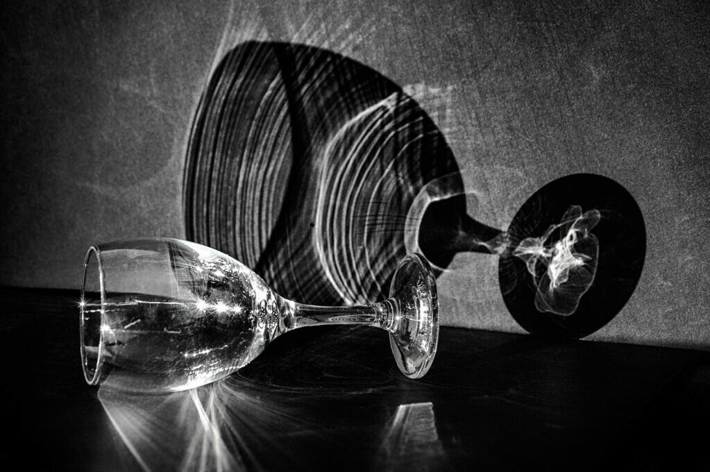 black and white photo of wine glass with its reflection