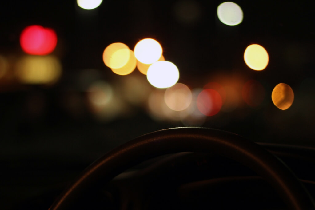 photo taken at night from interior of car of exterior lights with steering wheel in foreground