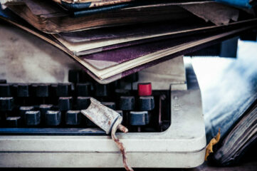 photo of typewriter with notebooks piled on top