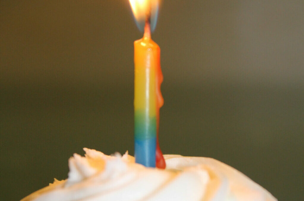 photo of chocolate cupcake with white icing and lit candle on top